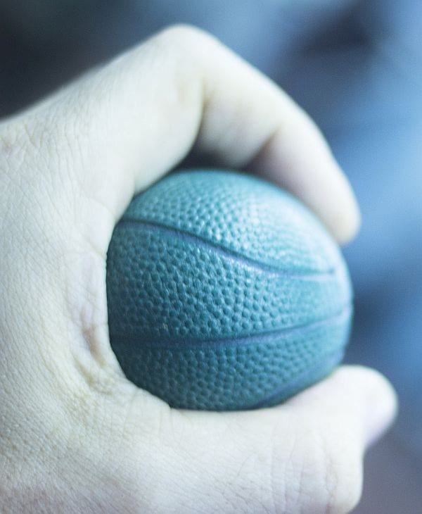 Wrist finger hand strength physiotherapy ball being held and compressed in sports injury physiotherapist medical center.
